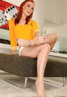 Рыжая красотка хвастается ножками с педикюром на пуфе 3 фотография