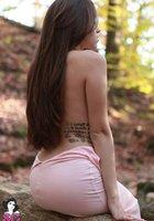 Молодая красотка с тату сняла розовое платье на природе 5 фотография