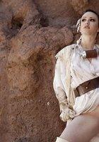 Странница в одежде из грязной ткани светит побритой пилоткой под скалой 3 фотография