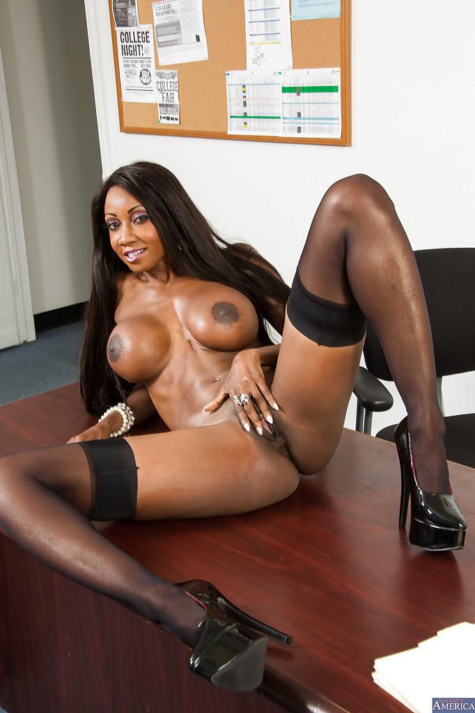 Чернокожая секретарша в чулках позирует на деревянном столе