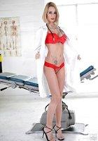 Врачиха со стетоскопом на шее снимает красное белье и позирует около кушетки 3 фотография