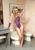 Молодая блондинка в фиолетовых митенках мастурбирует на белом унитазе 3 фотография