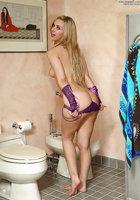Молодая блондинка в фиолетовых митенках мастурбирует на белом унитазе 5 фотография