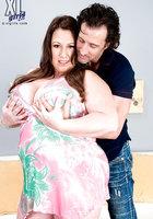 Крендель массирует большие груди толстушки и раздевает ее догола около дивана 2 фотография