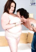 Крендель массирует большие груди толстушки и раздевает ее догола около дивана 8 фотография