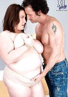 Крендель массирует большие груди толстушки и раздевает ее догола около дивана 9 фотография